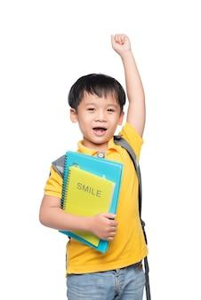 Portret uroczego uśmiechniętego chłopca z plecakiem i kolorowymi książkami z podniesioną ręką