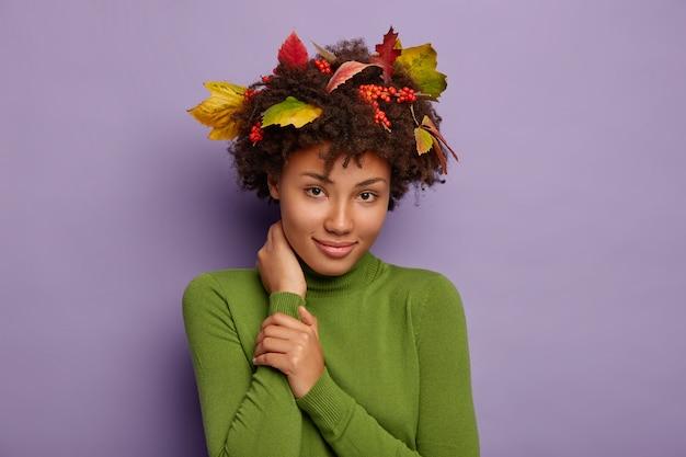 Portret uroczej afroamerykanki dotyka szyi, spokojnie patrzy w kamerę, nosi swobodny poloneck, jesienne liście, jagody w kręconych włosach, aby uzyskać idealną fryzurę, zadowolony