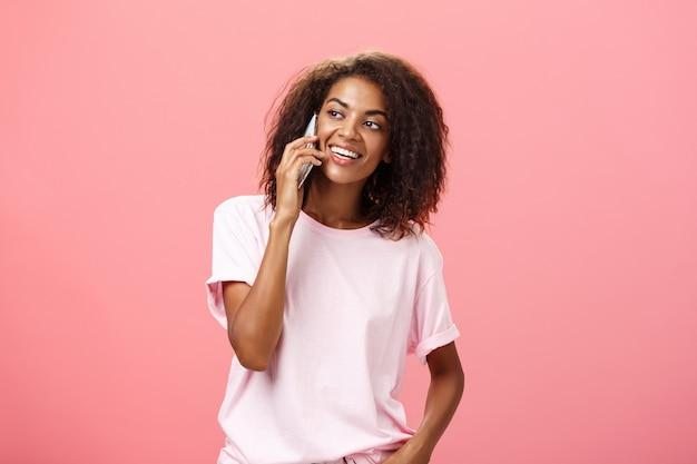 Portret uroczej afroamerykanki młodej kobiety z fryzurą afro, trzymając smartfon i patrząc w lewo z zaciekawieniem.