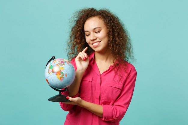 Portret uroczej afrykańskiej dziewczyny w ubraniach casual, trzymając w rękach globus ziemi na białym tle na niebieskim tle turkusu w studio. ludzie szczere emocje, koncepcja stylu życia. makieta miejsca na kopię.