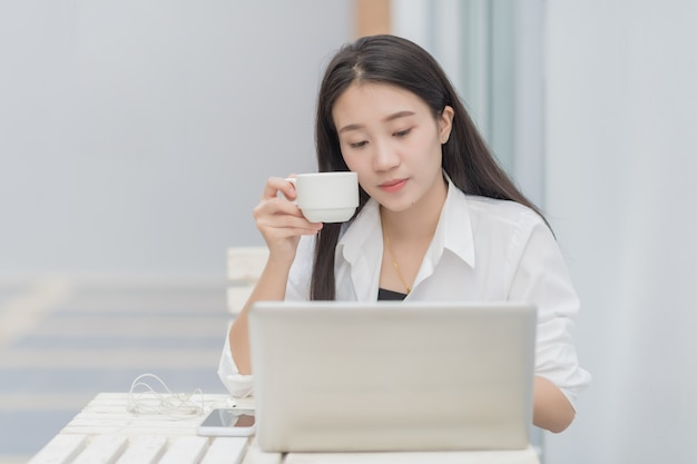 Portret uroczej azjatyckiej modelki używa laptopa do komunikacji online; szczęśliwej biznesowej kobiety napoju kawowy obsiadanie przy białym biurkiem.