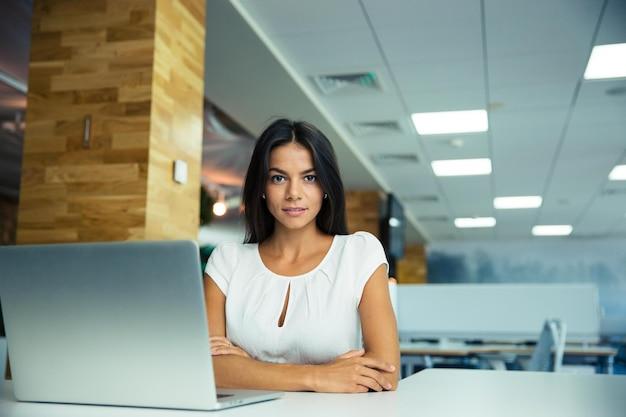 Portret uroczej bizneswoman siedzącej przy stole w nowoczesnym biurze
