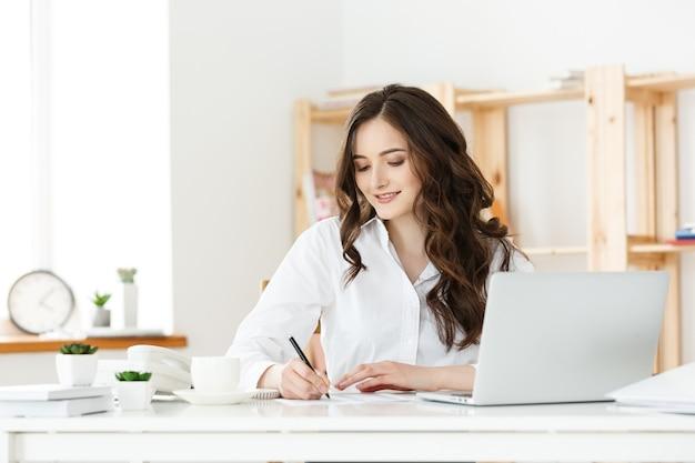 Portret uroczej bizneswoman siedzi w swoim miejscu pracy i pisze
