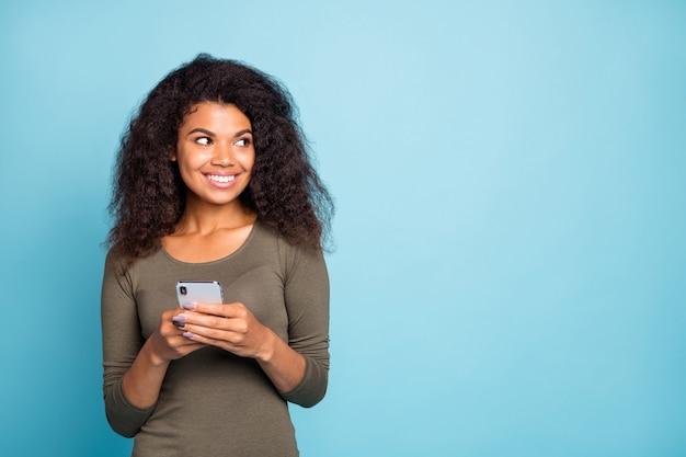 Portret uroczej blogerki o ciemnej skórze z wesołymi pozytywnymi emocjami trzymaj jej telefon komórkowy wyglądaj nosić strój w stylu casual odizolowany na niebieskiej ścianie