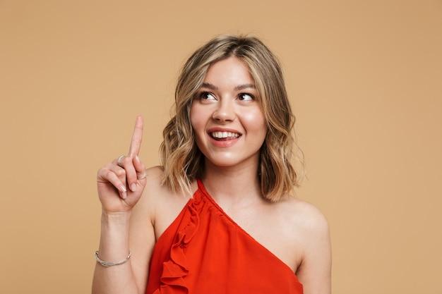Portret uroczej blondynki w sukience stojącej na białym tle nad beżową ścianą, wskazując palcem