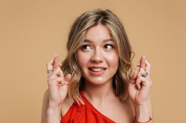 Portret uroczej blondynki w sukience stojącej odizolowanej na beżowej ścianie, trzymającej skrzyżowane palce