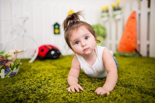Portret uroczej brązowookiej dziewczynki bawiącej się na dywanie w dziecięcym pokoju