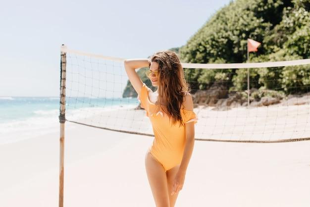 Portret uroczej brunetki dziewczyny stojącej w pobliżu zestawu do siatkówki. plenerowe zdjęcie przepięknej opalonej kobiety w pomarańczowym stroju kąpielowym czekającej na grę na plaży.