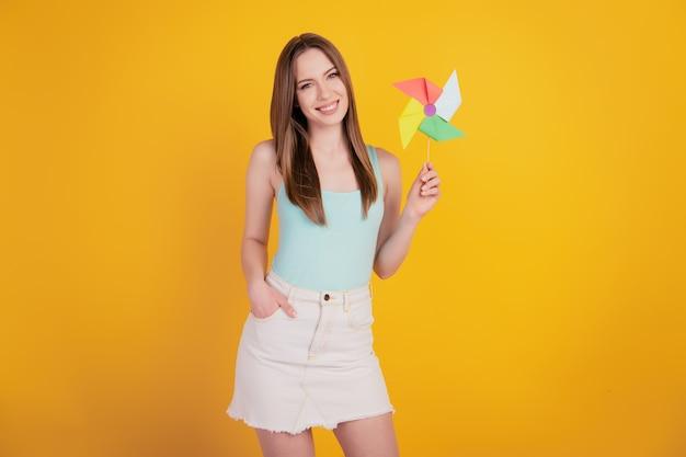 Portret uroczej dziecinnej słodkiej damy trzyma zabawkowe śmigło bawiące się na żółtym tle