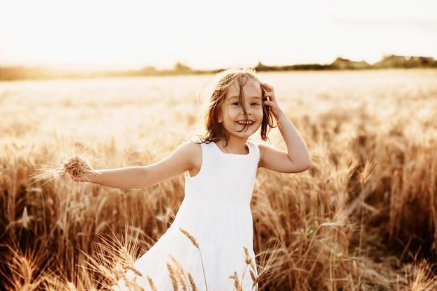 Portret uroczej dziewczynki grającej w jakim polu ubrana w białą sukienkę patrząc na kamery ze śmiechem.