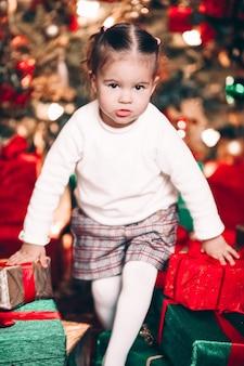 Portret uroczej dziewczynki otoczonej pięknie zapakowanymi prezentami świątecznymi