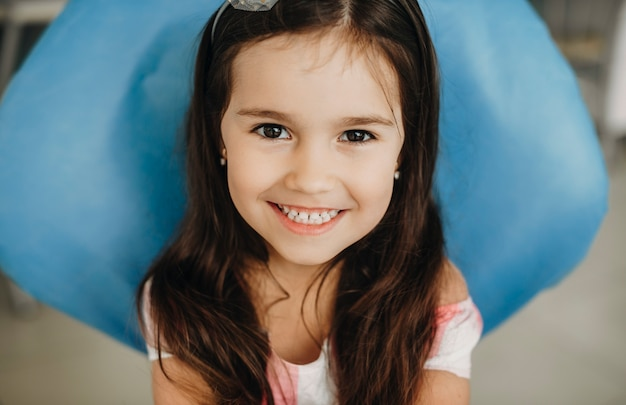 Portret uroczej dziewczynki siedzącej w stomatologii dziecięcej patrząc na kamery śmiejąc się przed operacją zębów.
