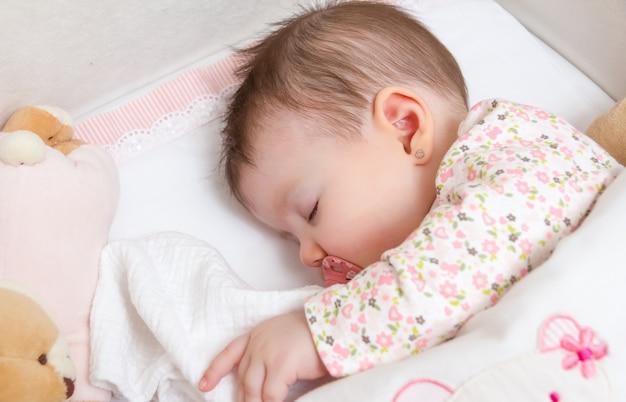 Portret uroczej dziewczynki śpiącej w łóżeczku ze smoczkiem i pluszową zabawką