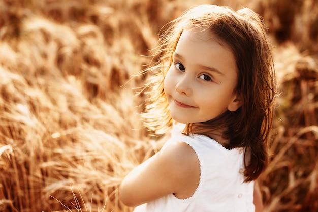 Portret uroczej dziewczynki ubrane w białą sukienkę dotykając pszenicy przed zachodem słońca uśmiechnięty.