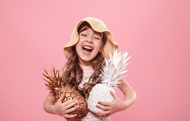 Portret uroczej dziewczynki w letnim kapeluszu, trzymającej dwa ananasy pomalowane na złoto i biało, koncepcja lata i kreatywności