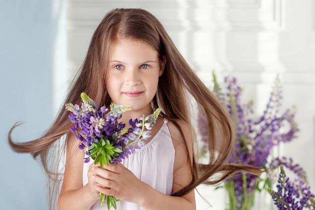 Portret uroczej dziewczynki z bukietem kwiatów. patrząc na aparat