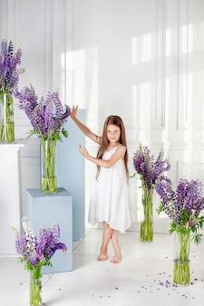Portret uroczej dziewczynki z kwiatami. dziewczyna śmieje się i bawi