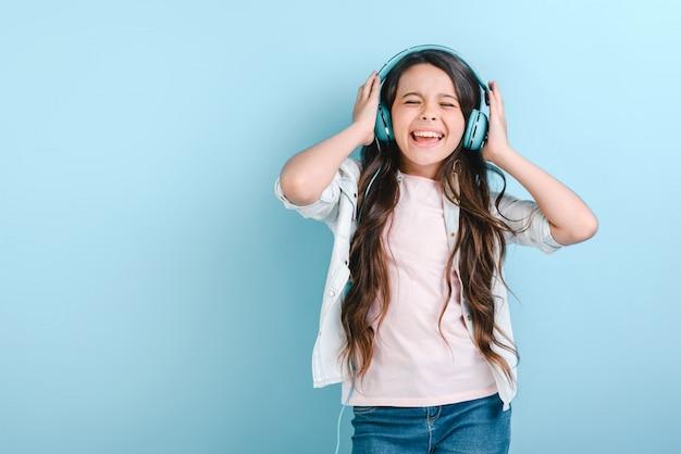 Portret uroczej dziewczynki z zamkniętymi oczami w słuchawkach słuchających muzyki i śpiewających dotyka jej głowy