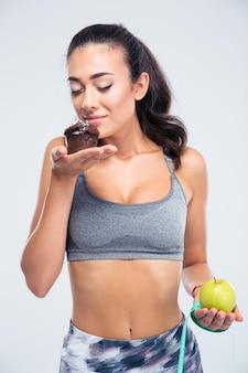 Portret uroczej dziewczyny fitness, wybierając między jabłkiem i ciastem na białym tle na białej ścianie