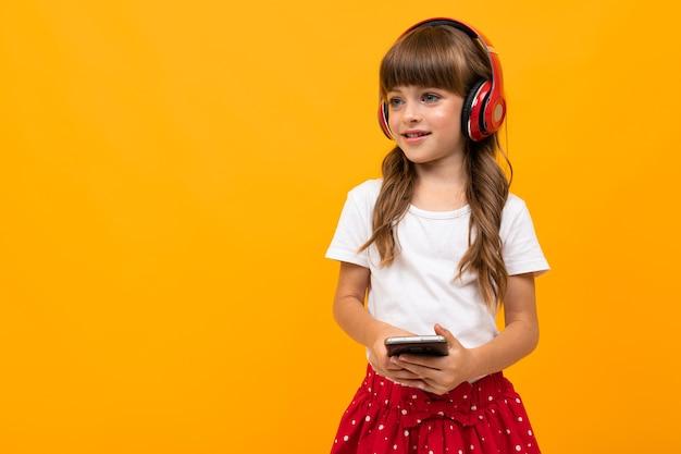 Portret uroczej dziewczyny rasy kaukaskiej z długimi kasztanowymi włosami i ładną buzią w biało-czerwonej sukience słucha muzyki z dużymi czerwonymi słuchawkami i uśmiecha się