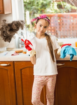 Portret uroczej dziewczyny sprzątanie bałaganu w kuchni za pomocą szmatki i pędzla