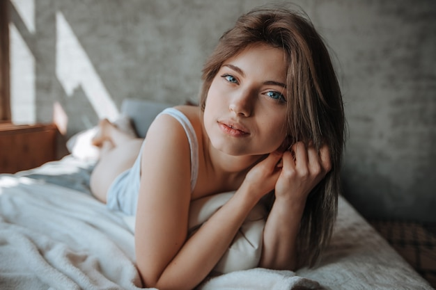 Portret uroczej dziewczyny z dużymi oczami leżącej na łóżku