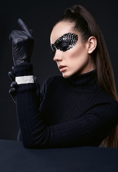 Portret uroczej eleganckiej brunetki kobiety w masce sweter z golfem i cekinami pozowanie na czarno w studio