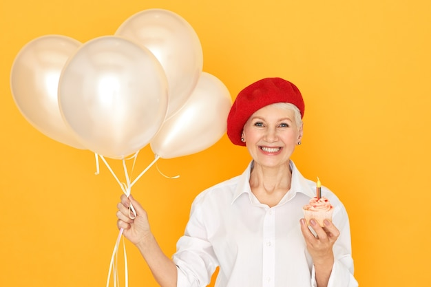 Portret uroczej eleganckiej kobiety na emeryturze w czerwonym berecie, pozowanie na białym tle z balonami i urodzinową babeczką z jedną świecą, wyrażając życzenie, uśmiechając się radośnie