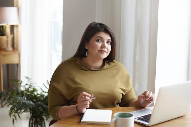 Portret uroczej eleganckiej młodej kobiety z pulchnymi policzkami i ciemnymi włosami, robiącej notatki w swoim zeszycie za pomocą bezprzewodowego połączenia internetowego na zwykłym przenośnym komputerze w biurze domowym