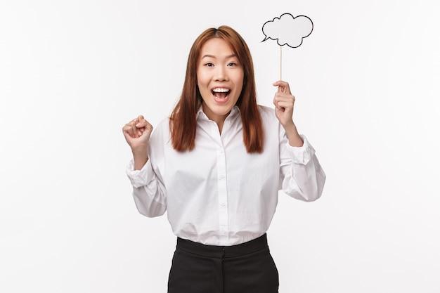 Portret uroczej i podekscytowanej azjatyckiej kobiety ma świetny pomysł, jest zainspirowany, trzyma chmurkę komentarzy na patyku z promiennym uśmiechem, dzieli się swoją myślą, białą ścianą