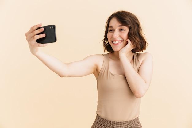 Portret uroczej kaukaskiej kobiety w wieku 20 lat, ubranej w zwykłe ubrania, uśmiechniętej podczas robienia zdjęcia selfie na telefonie komórkowym na białym tle