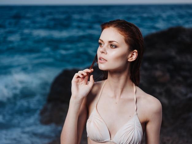 Portret uroczej kobiety model biały strój kąpielowy i błękitne morze białej piankowej plaży. wysokiej jakości zdjęcie