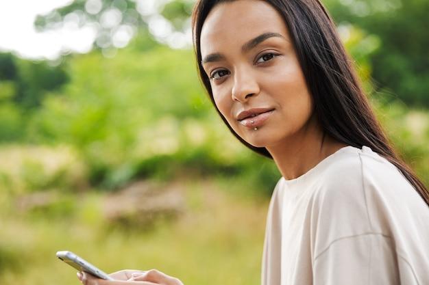 Portret uroczej kobiety noszącej piercing do ust, patrzącej na kamerę i trzymającej smartfona w zielonym parku