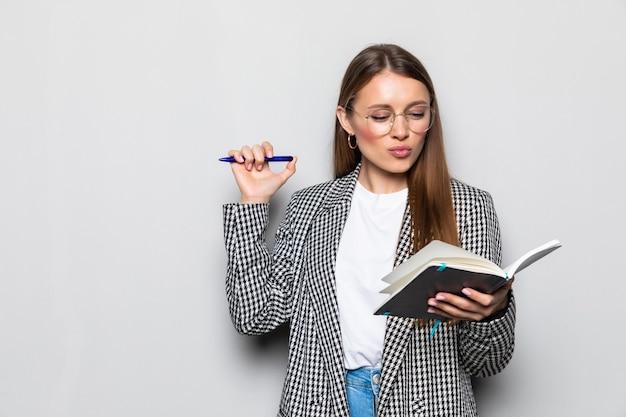 Portret uroczej kobiety o notatnik i długopis w rękach planowania, ekspertyzy, analizowania na białym tle