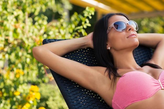 Portret uroczej kobiety opalającej się na leżaku na świeżym powietrzu