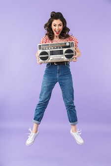 Portret uroczej kobiety pin-up w stylu amerykańskim, ciesząc się, trzymając stary vintage boombox na białym tle nad fioletową ścianą