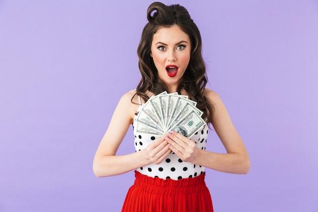 Portret uroczej kobiety pin-up w sukience vintage w kropki uśmiecha się trzymając kilka banknotów na białym tle nad fioletową ścianą