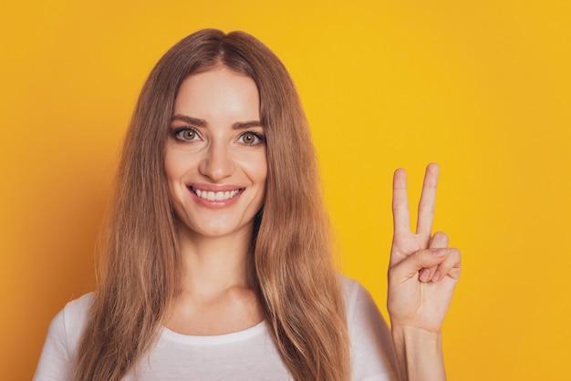Portret uroczej kobiety pokazującej znak v na żółtym tle