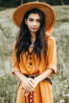 Portret uroczej kobiety rasy kaukaskiej z ciemnymi długimi włosami patrząc na kamery uśmiechnięty na sobie kapelusz oparty na gitarze na zewnątrz w naturze.