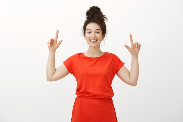 Portret uroczej kobiety szczęśliwy z kręconymi włosami w czerwonej sukience