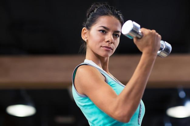 Portret uroczej kobiety treningu z hantlami w siłowni fitness