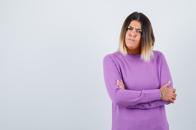 Portret uroczej kobiety trzymającej ręce złożone w fioletowy sweter i patrzącej na zamyślony widok z przodu
