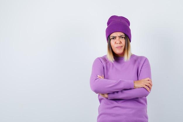 Portret uroczej kobiety trzymającej ręce złożone w swetrze, czapkę i niezadowolony widok z przodu