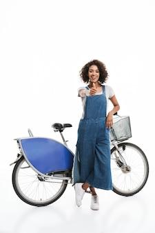 Portret uroczej kobiety ubranej w dżinsowe kombinezony, uśmiechniętej i pokazującej kciuk do góry, stojąc nad rowerem odizolowanym nad białą ścianą