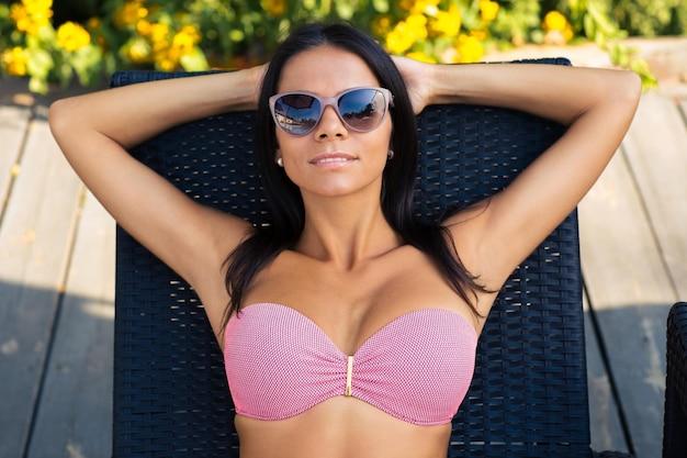 Portret uroczej kobiety w okularach przeciwsłonecznych opalającej się na leżaku na świeżym powietrzu