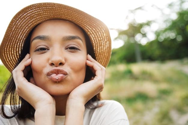 Portret uroczej kobiety w słomkowym kapeluszu i przekłuciu wargi robi pocałunek przed kamerą podczas spaceru w zielonym parku