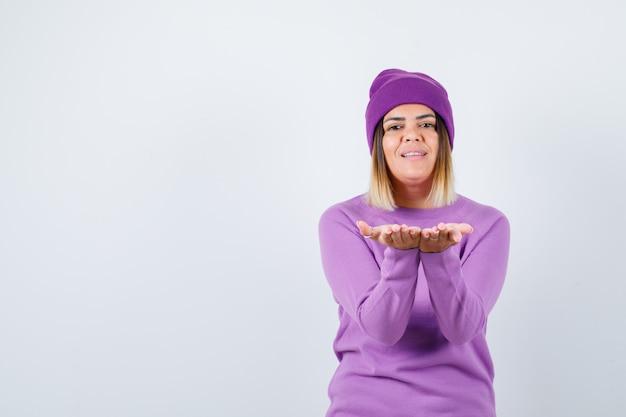 Portret uroczej kobiety wykonującej gest dający lub otrzymujący gest w swetrze, czapce i patrzący wesoły widok z przodu