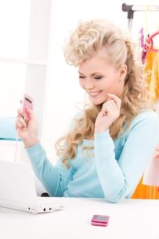 Portret uroczej kobiety z kalkulatorem i komputerem