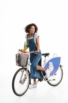 Portret uroczej kobiety z torbą na zakupy uśmiecha się podczas jazdy na rowerze na białym tle nad białą ścianą