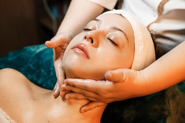 Portret uroczej kobiety z zamkniętymi oczami opierającej się na łóżku i wykonującej masaż karku w centrum odnowy biologicznej.